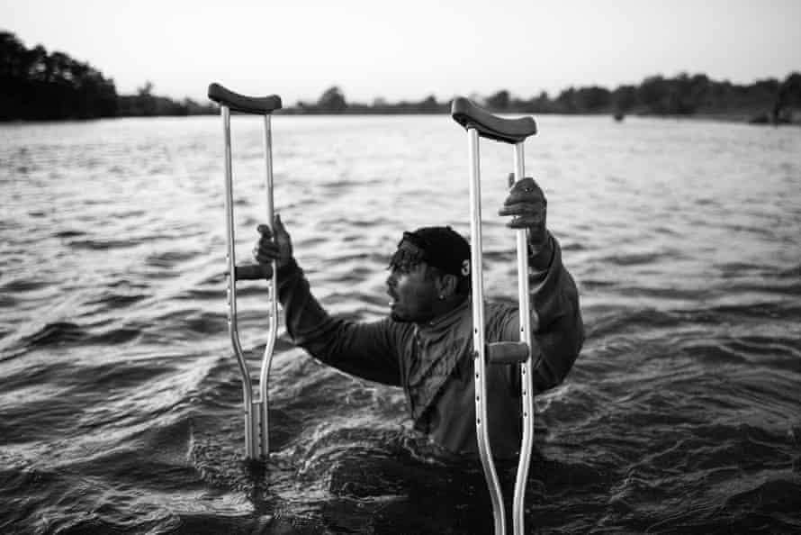 Having travelled across two countries in eight days, Joel, a Honduran with one leg, makes his way across the river with crutches, trying to keep up with the caravan
