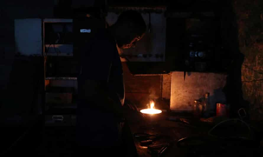 A man works inside a mechanical workshop during the blackout in Caracas on Friday.