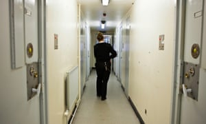 A prison officer walks past several locked cells in a corridor