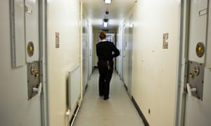 A female prison officer walks down the corridor of one of the residential wings at HMP Send.