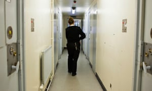 Prison officer walking down a corridor