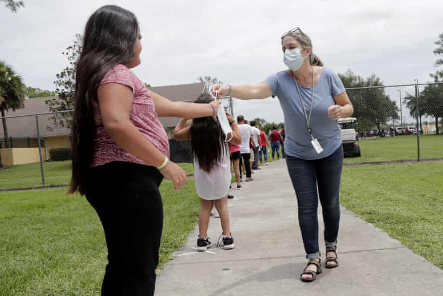 A woman passes out masks to people standing in line for Covid testing in Immokalee, Florida, on 7 June 2020.