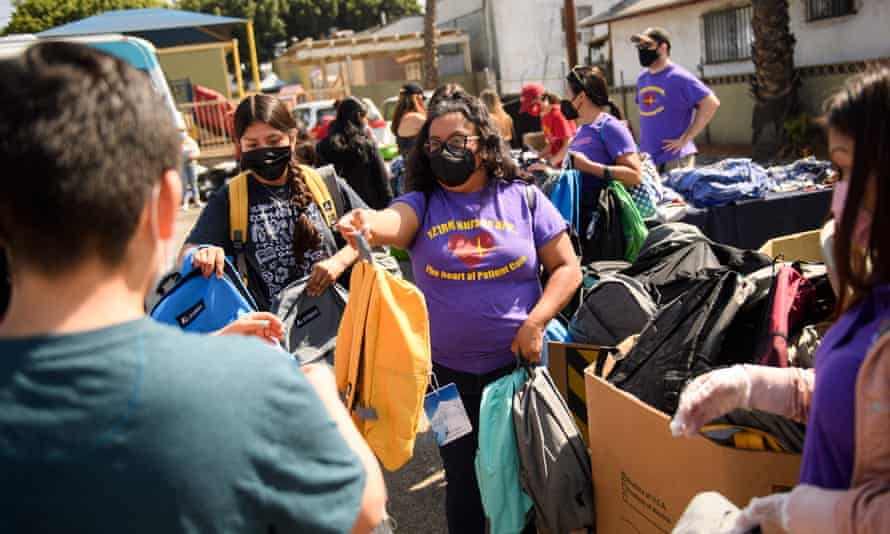 Nurses and healthcare workers with the Service Employees International Union (SEIU) distribute backpacks with school supplies, face masks, and other resources in Los Angeles, 7 August 2021.