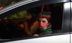 A woman dressed in the colours of Khan's PTI party is driven through the streets on election night.