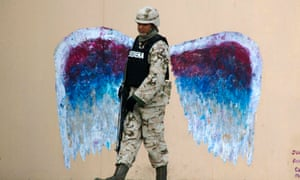 <strong>Ciudad Juarez, Mexico</strong><br>A soldier walks past graffiti depicting angel wings by artist Colette Miller