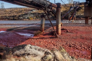 Bright red polluted water on the bank of the river Daldykan near the Russian city of Norilsk