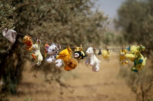 Children's toys hang from a laundry line near a group of tents, Daraa, Syria