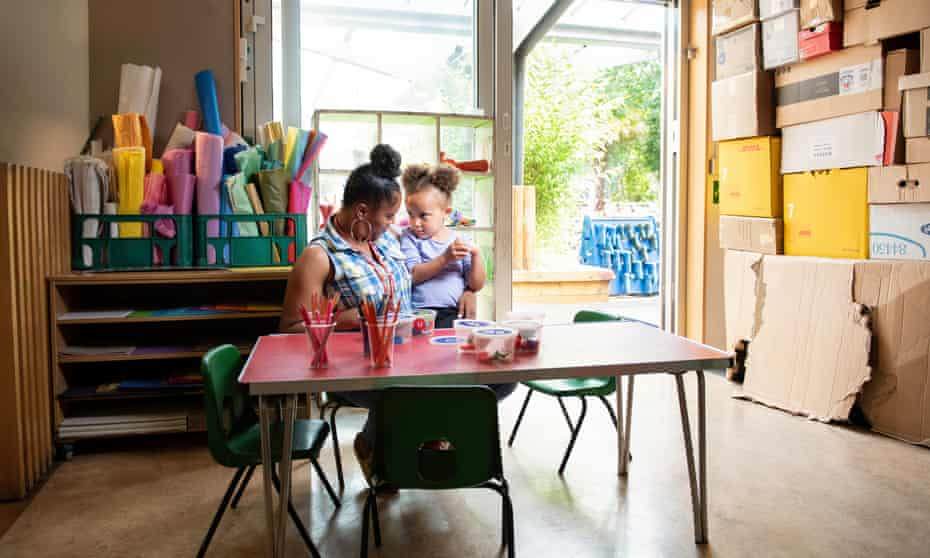 Tanisha Ogun, a nurse, sits with a child at a nursery in north London