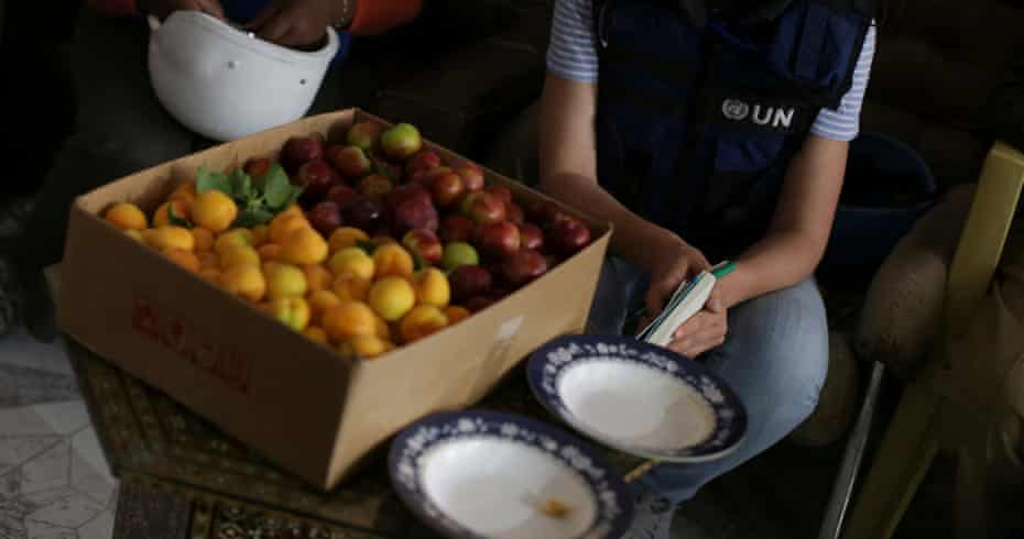 UN and World Food Programme staff sit beside a box of fruits in eastern Ghouta, in the Syrian capital Damascus.