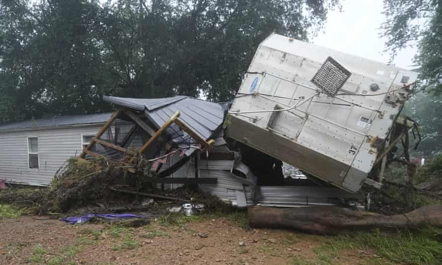 A mobile home and a truck trailer sit near a creek after they were washed away by flood waters in McEwen, Tennessee.