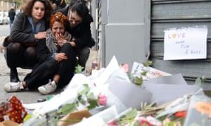 A woman cries near Le Petit Cambodge restaurant in Paris