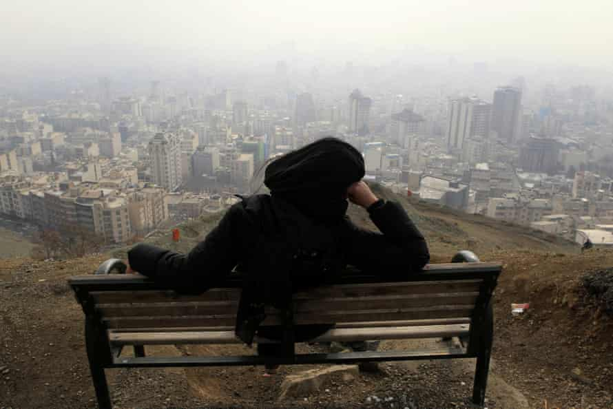 A woman in Tochal looks out at the polluted skyline of the Iranian capital, Tehran.