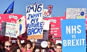 People hold placards and march to demand a people's vote against Brexit.