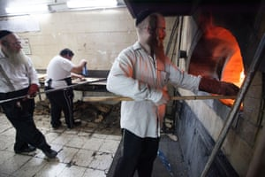 A worker is putting dough in a stone oven