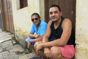 Two men in sit on a doorstep in Mariana, the town where the dam is sited