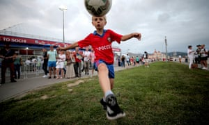 A young Russian fan juggles a ball as fans arrive for the semi-final between Germany and Mexico.