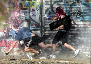A demonstrator falls as he and others run away from a riot police water cannon during a protest against the government of Chilean president Sebastián Piñera, in Santiago, on 06 December 2019
