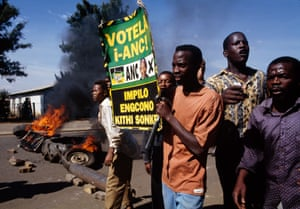 Supporters of the ANC and its leader, Nelson Mandela, put up burning barricades in Thokoza township, south of Johannesburg, amid gun battles with rival Inkatha fighters during the run-up to South Africa's first democratic elections in 1994. The image was taken on 18 April, the day that the photojournalist Ken Oosterbroek, a member of the Bang-Bang Club - a group of four conflict photographers - was killed while covering clashes between peacekeepers and ANC supporters in Thokoza.