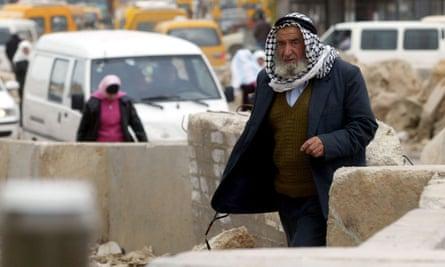 A Palestinian navigates cement blocks at an Israeli checkpoint.