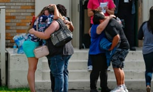People embrace outside the Alamo Gym where students and parents wait to reunite following a shooting at Santa Fe high school Friday.