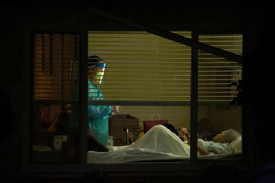 A healthcare worker attends to Susan Hailey, who has tested positive for coronavirus, at the Life Care Center of Kirkland.