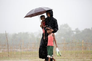Tombru, Bangladesh. A Rohingya woman stands in the rain with her children near a refugee camp close to the border between Myanmar and Bangladesh