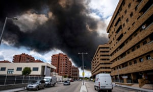 Black smoke from the vast tyre dump fire rises over a housing area in Toledo.