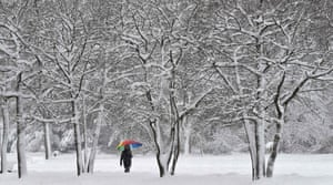 A pedestrian walks with an umbrella in a snow covered park in Munich, Germany.