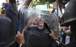 Security officers push back people during a protest held to show support to farmers who have been on a months-long protest in New Delhi.