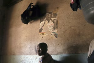 A young child passes by an old torn poster of former Zimbabwean President Robert Mugabein Harare.