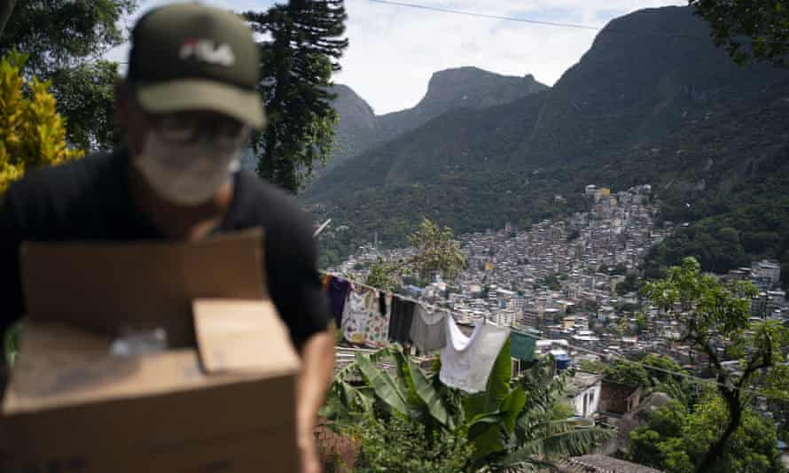 A local volunteer carries a package in the Rocinha favela. Brazil's death toll from coronavirus has risen in recent days.