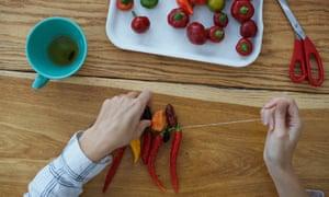 Stringing chillies.