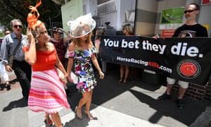 Racegoers walk past animal rights activists