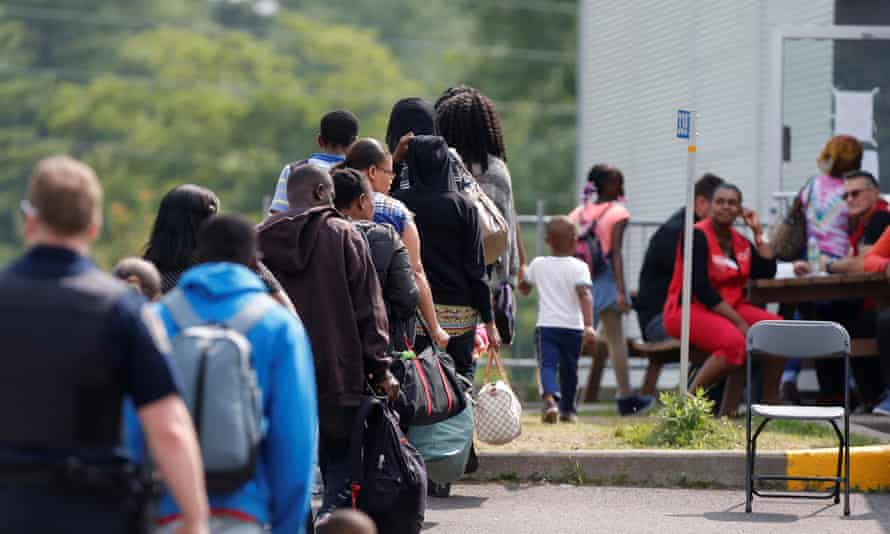 A group of asylum seekers wait to be processed in Lacolle, Quebec, Canada on 11 August 2017.