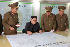 In pictures released on Tuesday, Kim Jong-un studies maps showing the path of a missile from North Korea to Guam.
