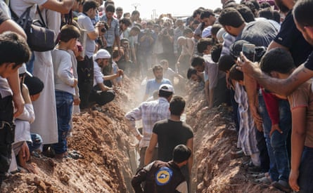 Members of the Syrian civil defence volunteers bury their fellow comrades during a funeral in Sarmin on Saturday.