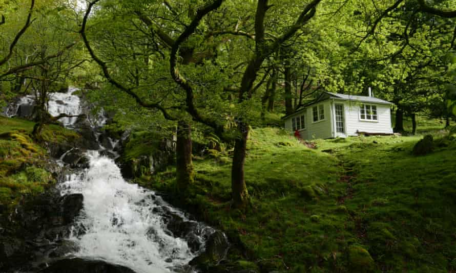 A cosy wooden cottage by a stream in Snowdonia.