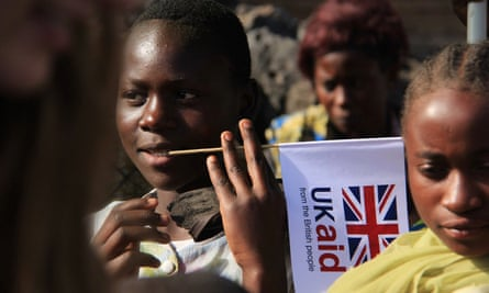 A child in the Democratic Republic of the Congo is seen holding a UK aid flag