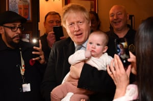 The prime minister, Boris Johnson, holds a baby at the Lynch Gate Tavern as he campaigns ahead of the general election in Wolverhampton, UK