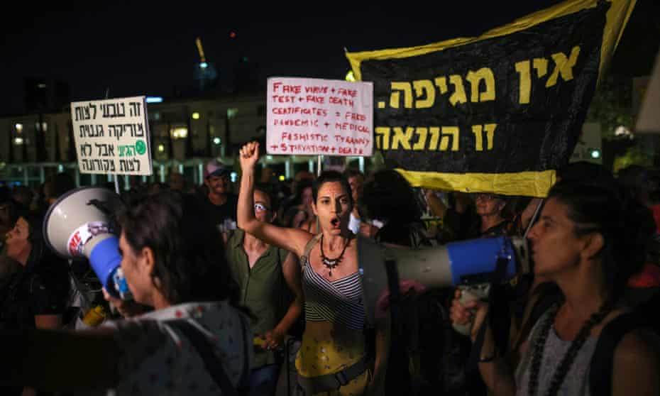 Protesters chant slogans denouncing the government's renewed coronavirus restrictions in Tel Aviv.
