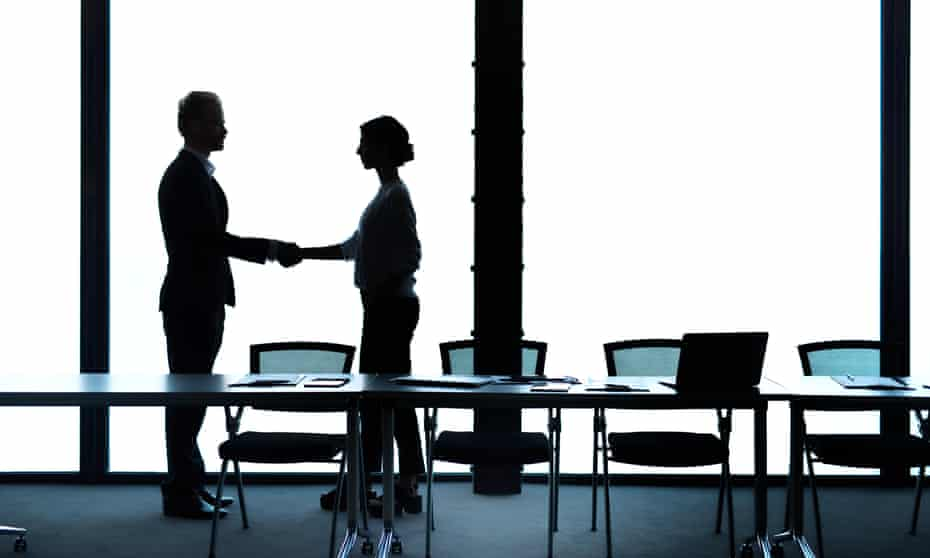 Silhouetted man and women shaking hands in boardroom