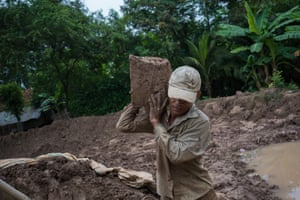 Phala, a debt-bonded brick worker, excavates clay from rural land for brick-making