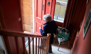 An older woman opening a front door to leave the house