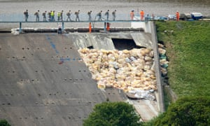 Army members cross the partially collapsed dam wall at Toddbrook Reservoir, where work continues to sure-up and pump water from the reservoir above Whaley Bridge.