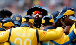 Thisara Perera, prepared for the fierce Yorkshire sunshine, and his teammates huddle together before the England innings at Headingley.