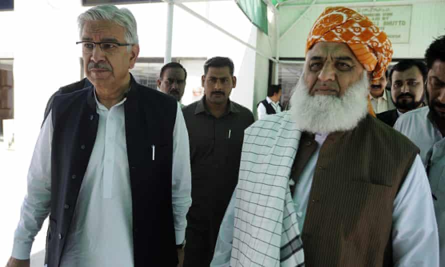 Pakistan's defence minister, Khawaja Muhammad Asif (L), with Maulana Fazlur Rehman (R), chief of the Jamiat Ulema-e-Islam Fazal party, outside parliament house in Islamabad