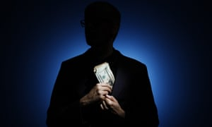 Silhouette of a man putting a large bundle of banknotes in his jacket