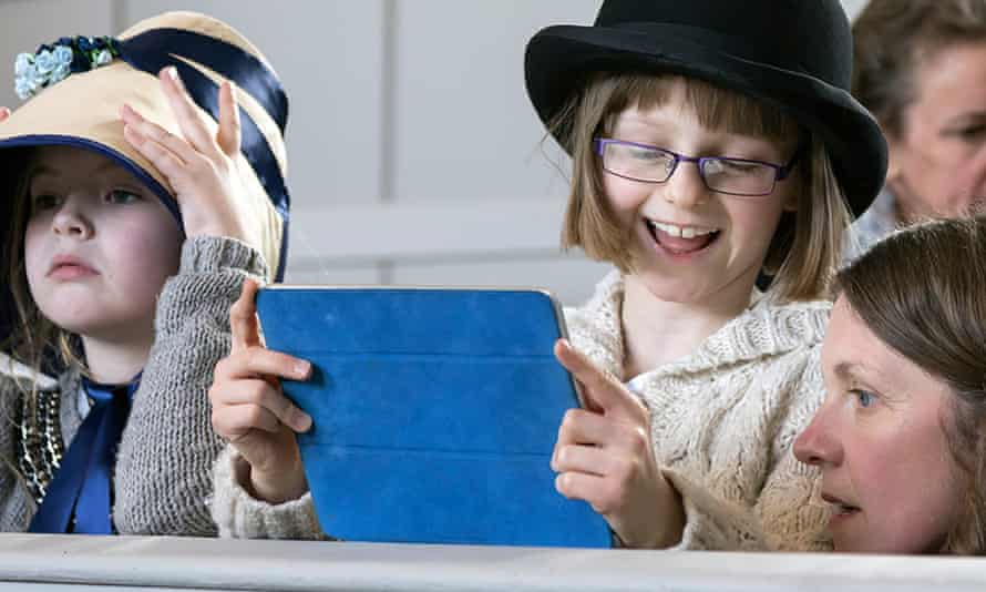 Children in the Shire Hall Historic Courthouse in Dorchester, Dorset, using an interactive guide on a tablet device, while dressed in 19th-century costume.