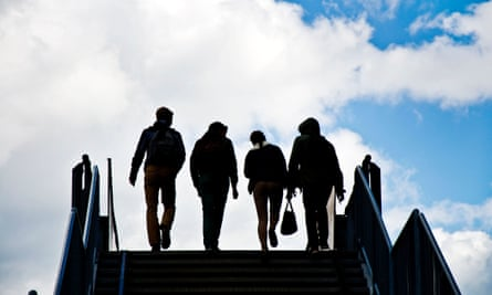 Silhouettes of young people crossing a bridge