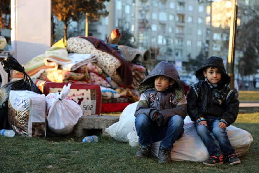 Children wait with their belongings as some thousands of people flee from the historic Sur district of the mainly-Kurdish city of Diyarbakir.